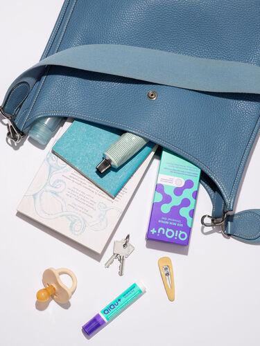 Ein QiQu Skin Repair Dispenser in einer Handtasche