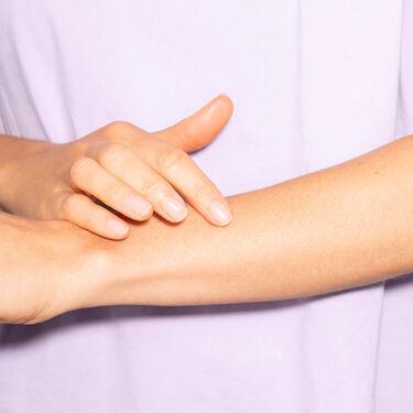 Person trägt QiQu Skin Repair am Arm auf