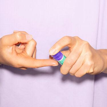Person trägt einen Tropfen QiQu Sin Repair auf dem Finger auf